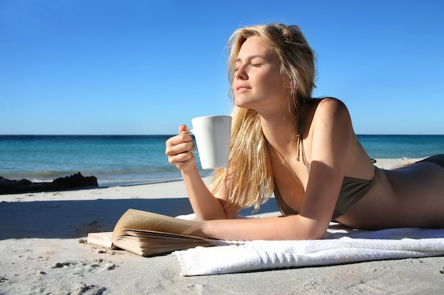 Hermosa chica rubia bebiendo una taza de café y leyendo un libro en la playa