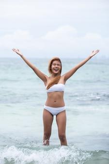 Hermosa chica rubia en bikini blanco en el mar.