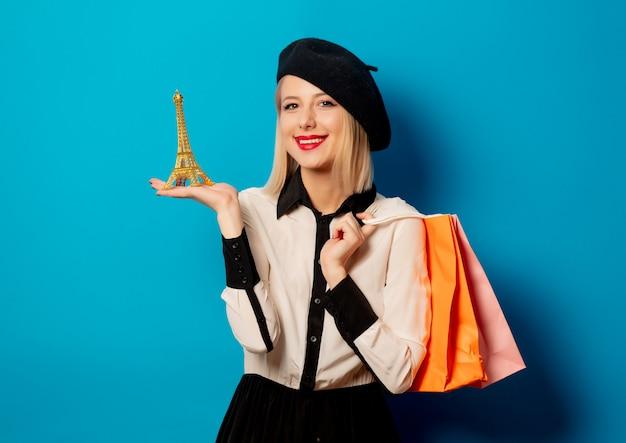 Hermosa chica rubia con bolsas de compras y la torre eiffel en la pared azul
