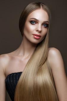 Hermosa chica rubia con un cabello perfectamente liso, maquillaje clásico. cara de belleza