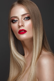 Hermosa chica rubia con un cabello perfectamente liso, maquillaje clásico y labios rojos. cara de belleza