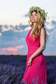 Hermosa chica rubia en el campo de lavanda al atardecer