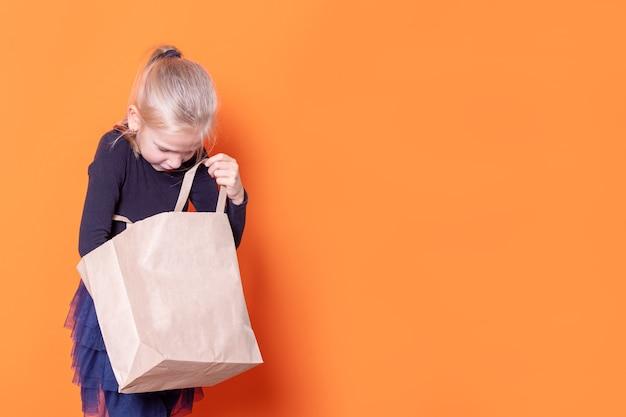 Una hermosa chica rubia caucásica con un vestido negro se ve en una bolsa de papel artesanal abierta sobre un fondo naranja. la niña saca un regalo del paquete. concepto de viernes negro. concepto de venta
