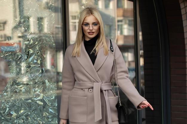 Hermosa chica rubia en una ciudad. elegante mujer con un abrigo. sonriente.