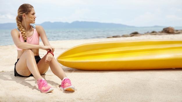 Hermosa chica rubia con cuerpo atlético relajante después de una larga carrera, pasar vacaciones en un país tropical.