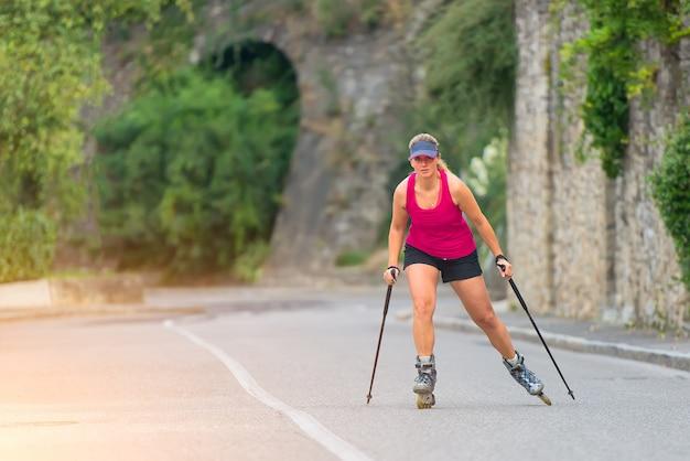 Hermosa chica rubia deportiva con patines y palo de escalada
