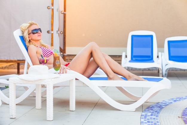 Hermosa chica rubia descansa cerca de la piscina
