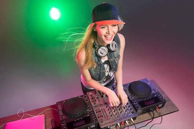 Hermosa chica rubia dj en cubiertas en la fiesta en el fondo de humo multicolor