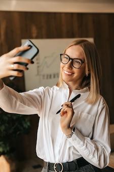 Una hermosa chica rubia feliz está transmitiendo una conversación en vivo a través del teléfono.