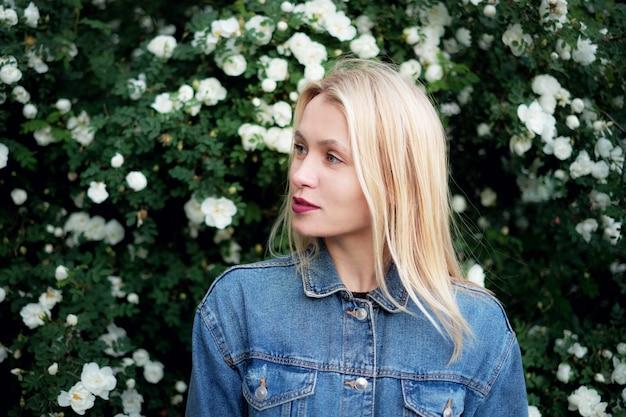 Una hermosa chica rubia con flores blancas.