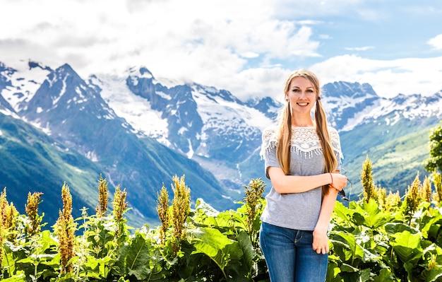 Hermosa chica rubia en el fondo del paisaje de las montañas