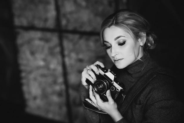 Hermosa chica rubia fotógrafo en estricto traje tiene en sus manos la vieja cámara retro. foto en blanco y negro.
