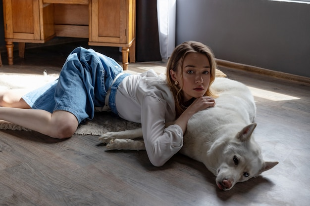 Hermosa chica rubia jugando con perro husky blanco