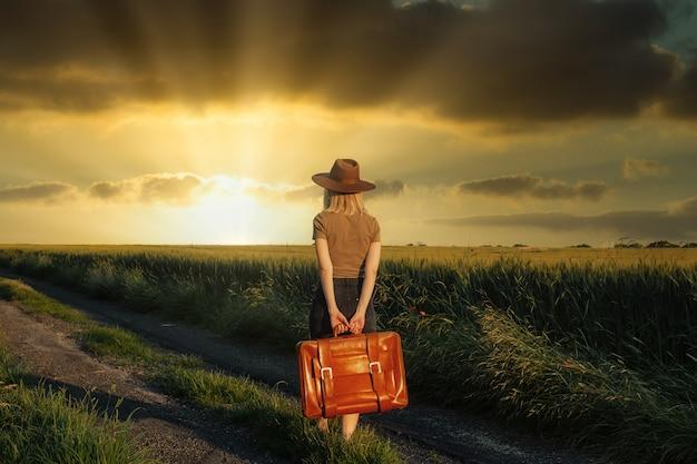 Hermosa chica rubia con maleta en camino de campo en el atardecer.