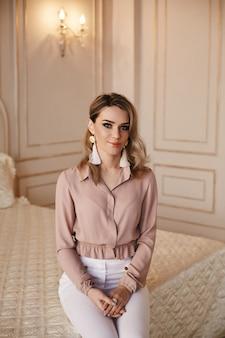 Hermosa chica rubia de moda en una blusa con aretes hechos a mano posan en el dormitorio