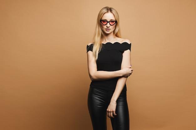 Hermosa chica rubia modelo con cuerpo sexy en pantalones de cuero negro de moda, en una blusa negra y en gafas de sol rosa de moda en la pared naranja, aislado