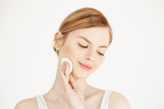Hermosa chica rubia natural limpieza cara con esponja de algodón sonriendo. cosmetología salud y spa.