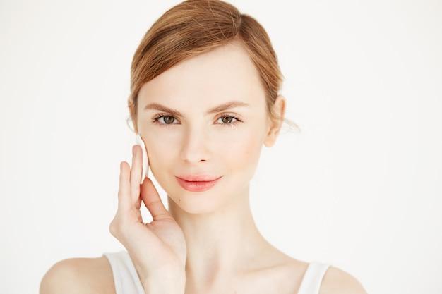 Hermosa chica rubia natural limpieza cara con esponja de algodón sonriendo. cosmetología y spa.