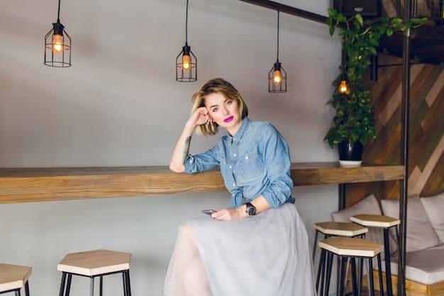 Hermosa chica rubia con ojos azules y labios rosados brillantes sentada en una cafetería en una silla. ella tiene un teléfono inteligente en la mano
