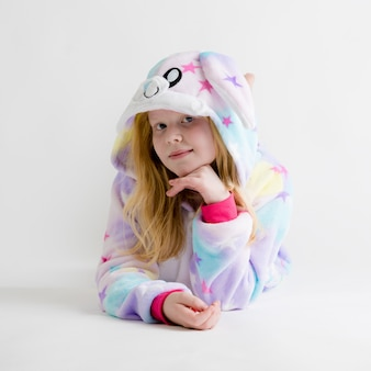 Hermosa chica rubia posando en blanco en pijama kigurumi, disfraz de conejito