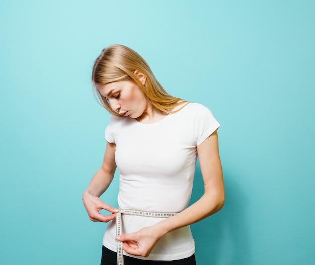 Una hermosa chica rubia que mide su cintura y está decepcionada con ella sobre un fondo azul.