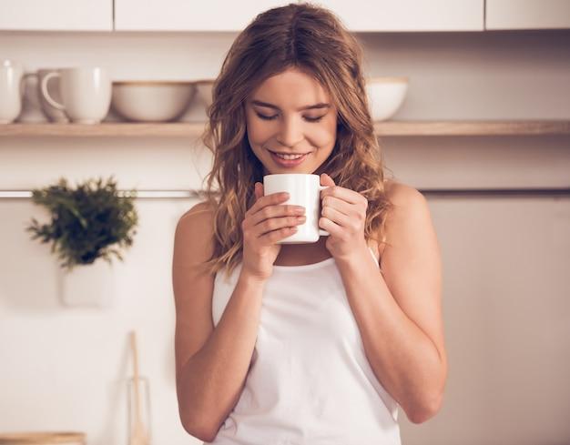 Hermosa chica rubia en ropa de casa está sosteniendo una taza