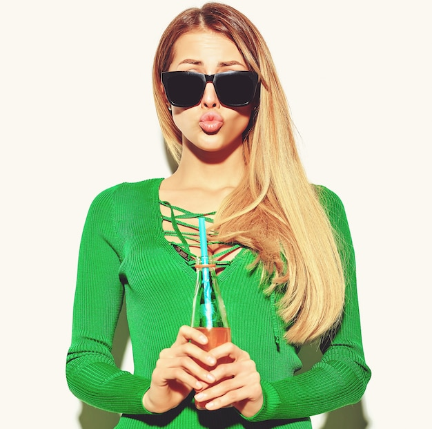 Hermosa chica rubia en ropa de verano casual hipster sin maquillaje aislado en blanco bebiendo cola de botella con paja dando un beso