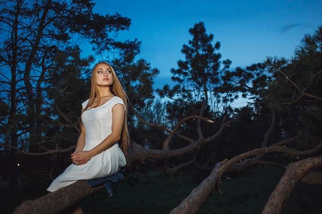 Hermosa chica rubia sentada en la rama de un árbol viejo en el bosque místico noche de hadas.