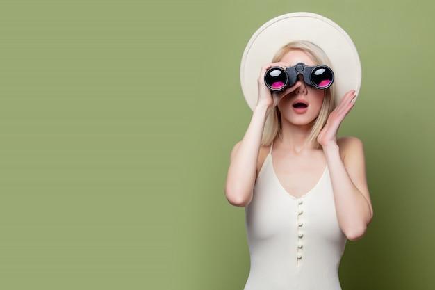Hermosa chica rubia con un sombrero blanco y vestido con binoculares