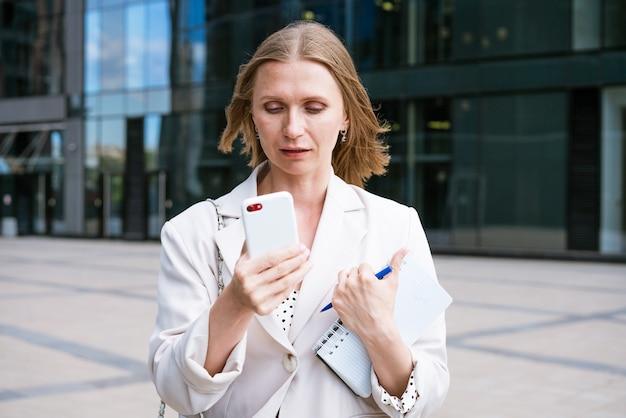 Una hermosa chica rubia sostiene un teléfono inteligente y un cuaderno en sus manos mujer de negocios usa un teléfono móvil ...