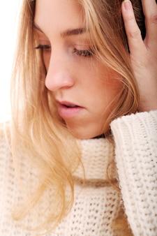Hermosa chica rubia en suéter de punto