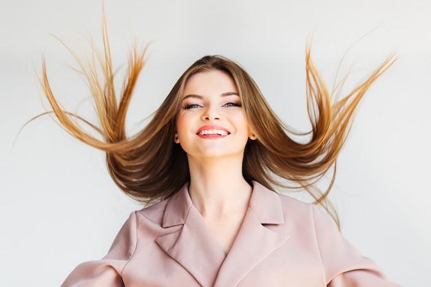 Hermosa chica rubia tirando su cabello en movimiento y mirando a la cámara sobre fondo blanco.