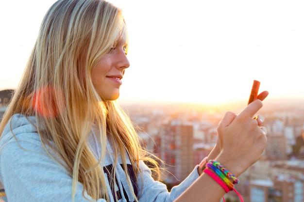 Hermosa chica rubia tomar fotos de la ciudad.