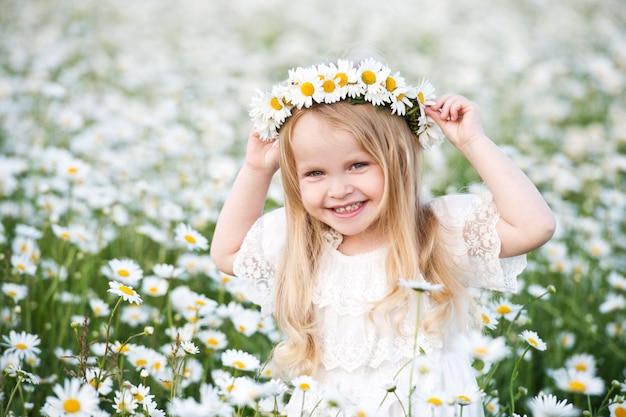 Hermosa chica con rubio hairand guirnalda de manzanilla en campo de manzanilla. retrato de niña linda con ramo de flores de manzanilla en día soleado de verano.