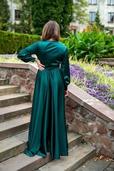 Hermosa chica sensual con vestido verde largo elegante de pie en los escalones del edificio