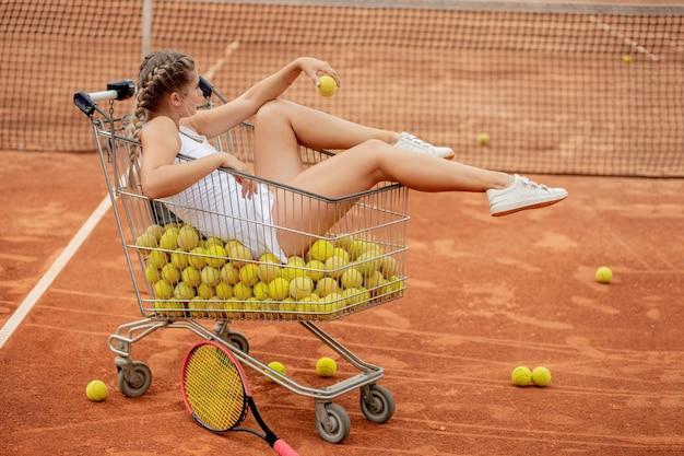 Hermosa chica sentada en la canasta de pelotas de tenis sosteniendo pelotas de tenis