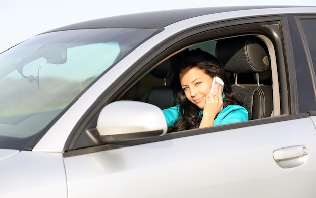 Hermosa chica sentada en un coche y hablando por teléfono