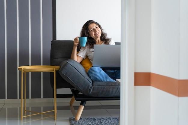 Hermosa chica sentada con un ordenador portátil en un sofá en una habitación elegante. trabajar desde casa. ambiente de trabajo de buen humor.
