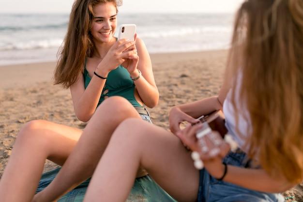 Hermosa chica sentada en la orilla del mar tomando selfie de su amigo jugando ukulele