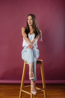 Hermosa chica sexy posando en el estudio en una silla. moda