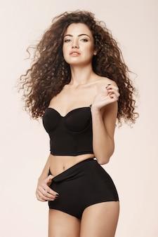 Hermosa chica sexy en ropa interior retro negra sobre pared rosa