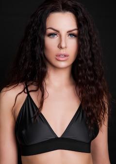Hermosa chica sexy con sujetador de seda negro sobre negro