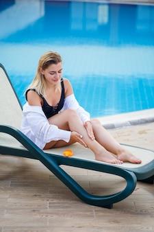 Hermosa chica sexy en traje de baño negro se sienta junto a la piscina y se aplica protector solar a su cuerpo
