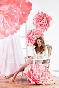 Hermosa chica sexy en un vestido largo con unas enormes flores rosas sentadas junto a la ventana