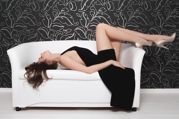 Hermosa chica sexy con vestido de noche negro en un sofá blanco
