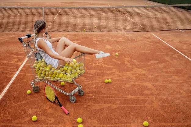 Hermosa chica se sienta en la canasta de pelotas de tenis mientras sostiene pelotas de tenis y raqueta en la mano.