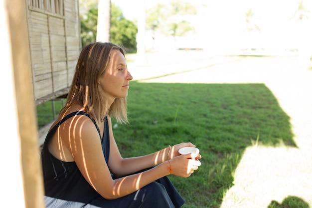 Hermosa chica se sienta cerca del bungalow y bebe café.