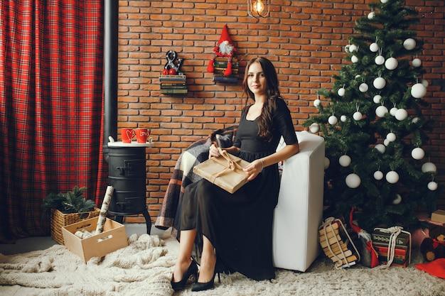 Hermosa chica se sienta en una sala de navidad