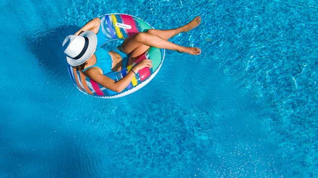Hermosa chica con sombrero en la piscina