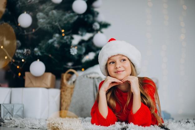 Hermosa chica con sombrero de santa bajo el árbol de navidad